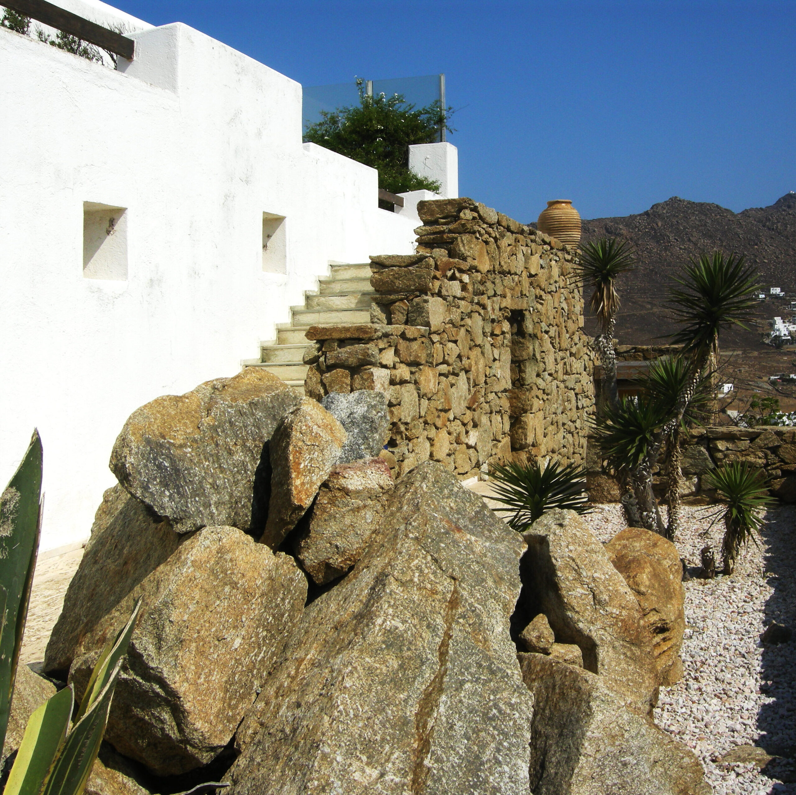 White walls an stone stairways to the pool